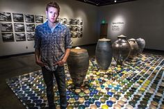 "Art major Ian Wilkinson by his ceramic pieces in the UAF Fine Arts gallery. His BFA thesis project, Spheres of Influence, raised more than $18,000 for the Fairbanks Food Bank through the sale of his 1,200 bowls.  <div class=""ss-paypal-button"">Filename: AAR-13-3775-153.jpg</div><div class=""ss-paypal-button-end"" style=""""></div>"