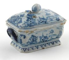 A rare Dutch Delft small box and cover 18th century, painted in blue with boats and buildings, the cover with a fruit knop, painted mark for De Klaeuw (The Claw) factory
