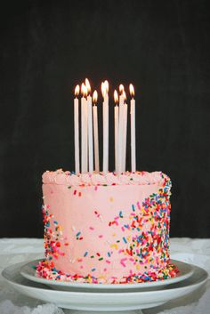 Pink birthday cake with sprinkles & lit candles