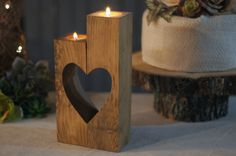 """Reclaimed Wooden Cube Candle Holder Set of 2 Tealight Holders with heart cut-out. Stained a warm chestnut. Approx Measurements: 4-6"""" in Height May have knots, cracks or imperfections. Looking to add s"""