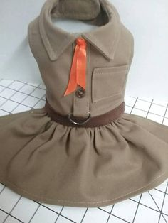Brownie doggie scout style dress with top stitched collar, pockets, leather look belt, wood look buttons and orange ribbon tie, gathered skirt, d ring. Neck and chest velcro closure. Badges and accessories can be purchased at another etsy shop. ( See photo) Not included with dress.