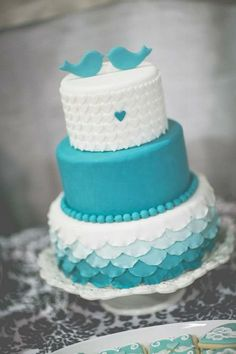 Teal bird chic wedding cake with hearts and petals. Love this cake!!