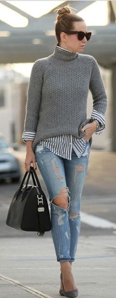 Gray sweater over striped blouse and blue jeans.