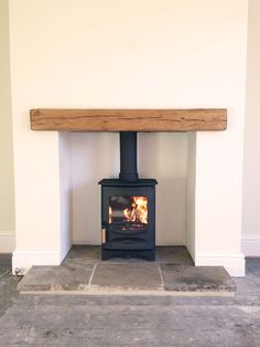 Image result for wood burning stove on flat wall with wooden mantle beam