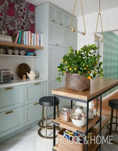 In H&H editorial director Alice Lawlor's galley kitchen, colorful cabinets and botanical wallpaper creates a modern look with an English twist. | Photographer: Alex Lukey | Designer: Sarah Hartill