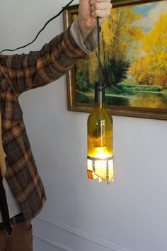 Stained glass wine bottle light  wine bottle with bottom cut off and stain glass soldered around the bottom edge, light fixture wired inside.