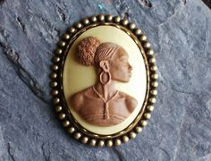 Beautiful brown cameo with a light tan background set in detailed antique brass. Cameo features a detailed African woman with broad shoulders, earrings and a necklace adorning her neck. Measures approx 2.25x 2 inches Secure, locking pin back Interested in more pieces with African cameos? Search African in my shop or follow the link below: https://www.etsy.com/shop/DelicateIndustry1?ref=hdr_shop_menu&search_query=african   You may return to the brooch section here…