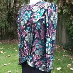 """VINTAGE Floral Blouse with Metallic Thread In excellent vintage condition. Colorful (purple, peach, teal, olive) metallic thread on a black background make up this stunning top. Tulip style overlapping front, back keyhole closure at the neck. Shoulder pads with 3 decorative buttons on the left shoulder. Print: 70% rayon, 30% metallic. Solid: 100% polyester. Dry clean only.  Pit to pit: 21"""" Shoulder: 16"""" Length: 27"""" 3/4 sleeve: 23"""" Vintage Tops Blouses"""