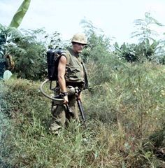 Soldier carrying between other weapons the M2A1 Portable Flamethrower.