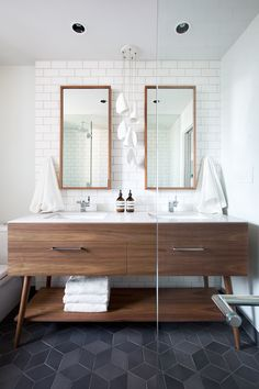 Interior Design by Falken Reynolds - Vancouver loft ensuite bathroom with American Mid Century Modern inspired walnut double vanity, Caesarstone counters, framed recessed medicine cabinets, white subway tile walls, Mutina Ceramics black Tex hexagon tile floors, Bocci 21 pendant, photo by Ema Peter