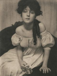 "This image is entitled, ""Portrait (Miss N)"" by artist Getrude Käsebier. ""Miss N"" refers to Evelyn Nesbit (1884-1967), a stage actress and renowned beauty whose longtime affair with acclaimed architect Stanford White began when they were 16 and 47, respectively and ended when Nesbit's husband, Harry Thaw, murdered White. Nesbit here embodies the qualities of both youthful innocence and the femme-fatale, characteristic of turn-of-the century symbolist depictions of womanhood."