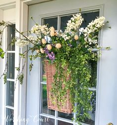 For an alternative to a traditional wreath, use a hanging basket filled with stems and greenery. #frontporchideas #frontporchdecorations #frontporchplanters #frontporchspringdecor #curbappeal #springwreath #springdecoratingideas #summerwreath #outdoordecor #frontdoordecor #wreathideas