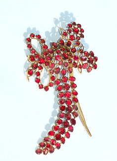 Garnet aigrette hair ornament, circa 1770, of faceted and rose-foiled almandine garnets in closed back gilt metal settings. The hair comb is attached to a spring, so that the aigrette moves en tremblant when worn in the hair. The aigrette measures 3 and 1/3 inches by 2 and 1/3 inches