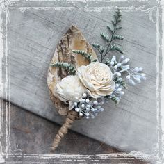 "Our handsome Birch Forest Boutonniere was inspired by the beauty of birch bark. Constructed with beautiful sola flowers, misty blooms, eucalyptus ""jacks"", and a hand cut birch bark leaf. Coordinates perfectly with lots of wedding styles, including woodland weddings, and winter wonderland nuptials. Wrapped with a lovely neutral twine. Rustic, handsome, and loaded with elegance and charm.It is approx. 3 inches wide, and 3 1/2 inches long. It attaches with a pin, which is..."
