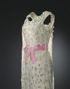 Vestido en crepé de seda de color beis con transparencia en tul mecánico verde de 1966. Perteneció a Mona Bismarck. Combina una doble silueta y el tul bordado deja entrever un vestido interior. Los lazos rosas en la cintura son recurrentes en las colecciones de Balenciaga.