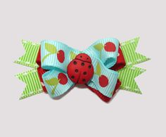 """#BTQM340 - Mini Boutique Bow Little Cherries, Ladybug on Blue Starting at: $5.39 Quantity in Cart: 1  Buy Now:   Add to Cart A adorable little bow!       This BowBiz Mini Boutique Bow features the following layers of ribbon: 1. Blue with Red Cherries 2. Red with White Dots 3. Green with White Edge Stitching Securely stitched to the center of this """"Little Cherries, Ladybug"""" mini boutique bow is a cute little red ladybug.   Size:  approx 1"""" x 1 3/4"""" for bow with flag back ribbons"""