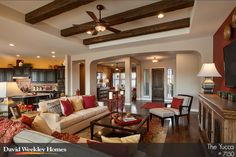 Exposed beams and spicy red accents make for a lively living room inside the Yucca by T.W. Lewis by David Weekley Homes. #arizona #realestate
