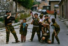Bosnian children, wearing camouflage military uniforms, play with toy weapons, including rifles and a bazooka, in the streets of Sarajevo