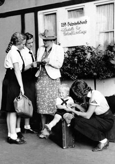 Girls of the German Girls League (BDM) help travelling women and children at the hitchhiker station in Berlin, in August in the station service of the National Socialist People's Welfare (NSV).