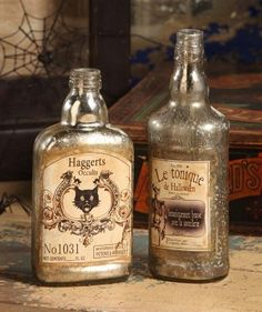 Antique Halloween Bottles (Medium) - Bethany Lowe – Black Bow Halloween Shoppe. Keep your potions safe in these beautiful vintage bottles.  Your Haggarts' brew and Le Tonique de Halloween can be paired with the Antique Halloween Bottles (Small) or Antique Halloween Bottles (Large) to create a creepy collection!  Sold as a set of 2 bottles.  Bethany Lowe. Glass with printed paper labels. 8 1/2″ and 7 1/4″.  FREE SHIPPING!!