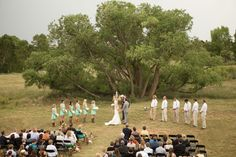 A big beautiful tree is the backdrop for this outdoor ceremony  (image: Andrea Dahlberg Photography).