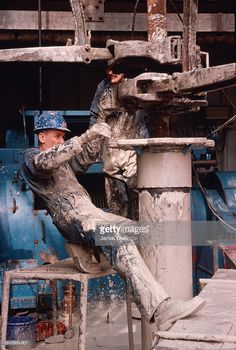 Stock Photo : Roughneck on oil rig using tong and 'running' thirteen inch casing