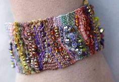 """How to make Cuff Bracelets video tutorial - Creativebug (free with trial). This cuff incorporates odds and ends of different yarn, fibers and beads. Liz teaches a freeform approach to looming, showing you how to set up a loom and basic weaving techniques with her """"over, under, over under"""" mantra. You design as you go, resulting in a modern asymmetrical, textured cuff."""