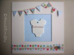 Baby bodysuit made from air dry clay and embossed. Mounted in a white box frame with bunting made from beautiful scrapbook papers, buttons and cord trim to decorate. These are made to order in your choice of colours for girls or boys and can be personalised ~ Price £20.00.