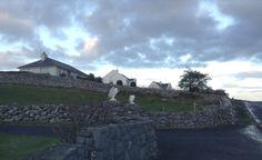 Irish farmhouse, stone wall and clouds.