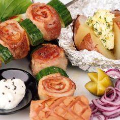 """A hússzeleteket klopfoljuk ki, sózzuk, enyhén borsozzuk, terítsünk rá egy-egy szelet sonkát, szorosan tekerjük fel, majd vágjuk szeletekre. Az apró """"csigákat"""" a feldarabolt zöldségekkel, hagymával váltogatva fűzzük nyársra.      A grillen forgatva 15-20 perc alatt süssük készre. A héjukban előfőzött burgonyákat rostlap fölött ismét forrósítsuk fel, közepüket kereszt alakban kissé metsszük be, végül a sóval és a zöldfűszerekkel ízesített vajjal töltsük meg."""