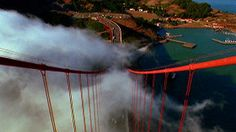 High angle view from top Golden Gate Bridge tower / fog moves thru suspension cables / traffic on road below