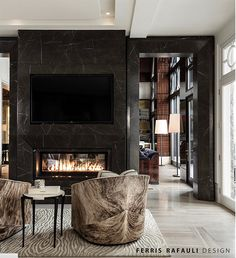 Black marble clads both the two-sided fireplace and archway here, adding a decidedly masculine feel to the room. | Designer: Ferris Rafauli