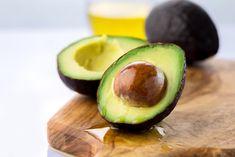 Gennemskåret avocado ligger på spækbræt
