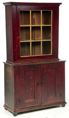 Stepback Cupboard, Ohio Mennonite, 3rd quarter-19th century, mixed woods including poplar and walnut. Two-piece, the upper section with one nine-pane door, the lower section with two paneled doors, all resting on recessed feet.