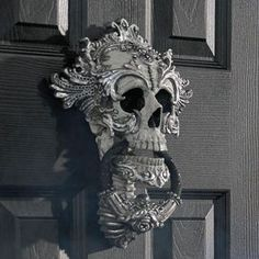 Skull Door Knocker. No shock the startlingly detailed design is from the renowned artists at Katherine's Collection. Realistic, life-size skull is masterfully hand painted, then elaborately embellished with intricate, metallic silver accents.