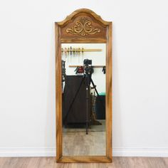 This mirror is featured in a solid wood with a glossy light oak finish. This wall mirror is in great condition with a curved top, acanthus leaf details and carved trim. Perfect for an entryway or hallway! #traditional #decor #mirror #sandiegovintage #vintagefurniture