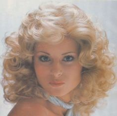 A big and soft loose curl from 1975, similar to the final hairstyle worn by Olivia Newton John in the film Grease