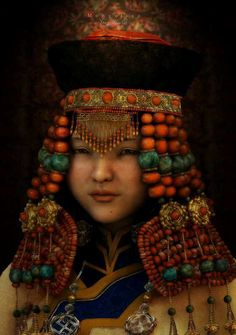 This girl from Mongolia, is wearing a traditional costume accessorized with silver and colorful gemstones