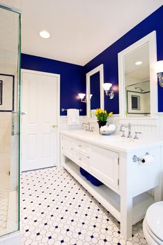 A final close view of the vanity reveals blue towels matching the upper wall tones, sitting on the lower open shelf. Chrome faucets match hardware throughout the space.