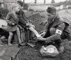 3.) A medic bandages a child's foot while his brother watches.