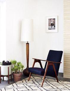 Un coin de salon avec du mobilier vintage des années 50 dans un univers bohème avec un tapis style marocain et les plantes vertes