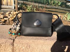 "Black Hip Bag — Collar Addict Not your old fanny pack. Welcome the Hip Bag. It's a 2"" wide belt with an attached bag 5"" x 3.75"" x .75"", fashionable D-rings and a concho that coordinates with our other pieces and dog collars... of course."