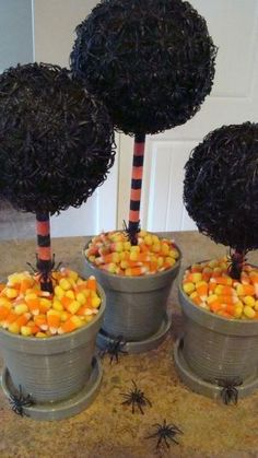 Spider Topiaries With Candy Corn Base {Image Only}. Looks like styrofoam ball painted black with spiders glued all over. Add painted dowel.