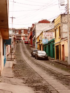 typical street scene in Quetzaltenango, Guatemala.  Lots of dust and dirt on cobblestone.  #xela #quetzaltenango