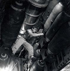 A crew member checks bombs inside the bomb bay of a B-29.