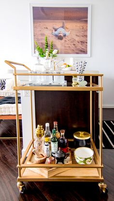 Gold bar cart with crystal glasses and striped straws and art of man on a beach