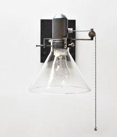 The Harrison pulley sconce is handmade from A36 raw steel. Components include stainless steel pulley with lock collar, stainless steel ball chain and stainless machine screws. Glass cone is fired and hand shaped Pyrex™ glass. $650