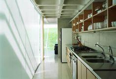 Casa Moderna em Aldeia da Serra por MMBB. Cozinha com armários sem portas, bancada de inox e parede de vidro. Laje de concreto aparente e piso de granilite cinza claro.