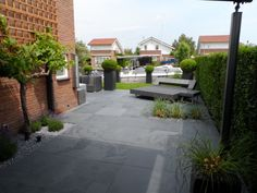 Mooie, onderhoudsvriendelijk terras met Leisteen Mustang Black terrastegels, door Natuursteen Meterik.