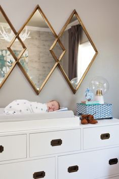 Awesome diamond shaped mirror above this nursery's campaign dresser. The baby is pretty darn cute too!